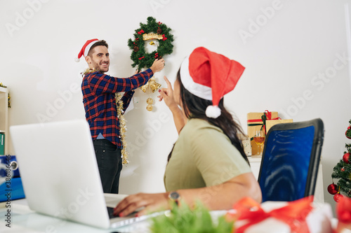 Obraz na plátně Businesswoman in Santa hat asking colleague to hang Christmas wreath on office w