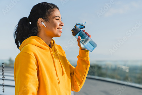 Valokuvatapetti Portrait of a 20s mixed race female runner being thirsty after work out drinking