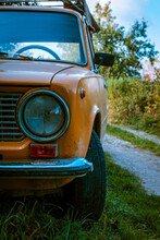 An Old Yellow Car In The Middle Of A Country Lane