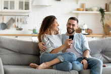 Happy Young Couple Using Smartphone Together, Relaxing On Cozy Couch At Home, Smiling Overjoyed Woman And Man Hugging, Enjoying Leisure Time With Gadget, Sitting On Sofa In Living Room