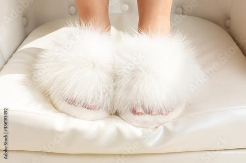 Obraz na plátně Beautiful fluffy fur slippers on women legs.