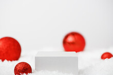 White Cube Pedestal On Snow On Winter Festive White Background. Light Christmas Scene With A Podium. Display Of Cosmetics And Beauty Products. Stand With New Year's Decor With Red Balls