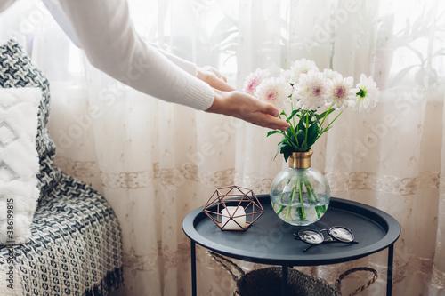 Billede på lærred Woman puts vase with flowers dahlias on table