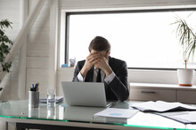 Unhappy Young Male Manager Covering Head With Hands, Suffering From Pressure At Work Or Feeling Unwell Due To Overload. Overworked Stressed Businessman Workaholic Having Headache, Needs Rest.