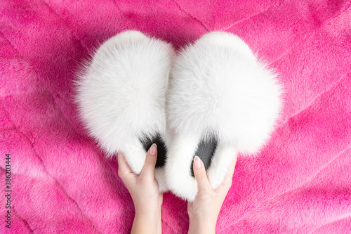 Fotografiet Female hands holding beautiful fur slippers on the fluffy fur plaid