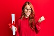 Leinwandbild Motiv Young redhead woman holding graduate degree diploma screaming proud, celebrating victory and success very excited with raised arms