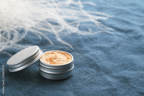 Jar of natural cosmetic product on blue linen fabric