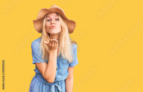 Fotografie, Obraz Young beautiful blonde woman wearing summer hat and dress looking at the camera blowing a kiss with hand on air being lovely and sexy