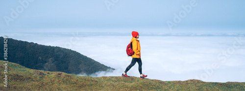Young female backpacker dressed orange waterproof jacket hiking by the mountain above the cloud route at the end of February on Madeira island, Portugal. Active people around World traveling concept.