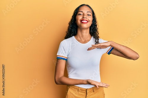 Young african american girl wearing casual clothes gesturing with hands showing big and large size sign, measure symbol Wallpaper Mural