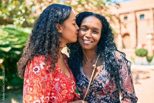 Obraz na plátně African american mother and daughter smiling happy hugging and kissing at the park