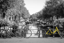 A Picture Of A Lonely Yellow Bike On The Bridge Over The Channel In Amsterdam. The Background Is Black And White.