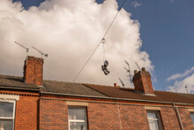 Old Sneakers Hanging From An Electricity Wire Against A Blue Sky With Clouds And Residential Building.