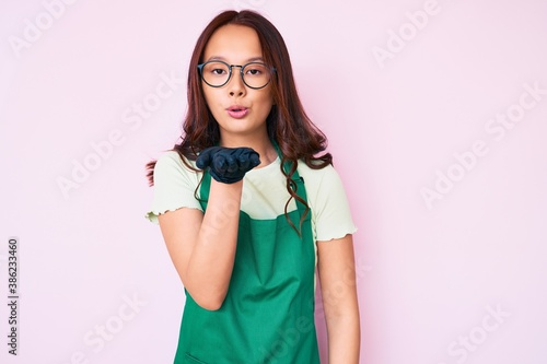Obraz na plátně Young beautiful chinese girl wearing cleaner apron looking at the camera blowing a kiss with hand on air being lovely and sexy