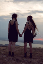 Two Woman In Black Dresses Wal...