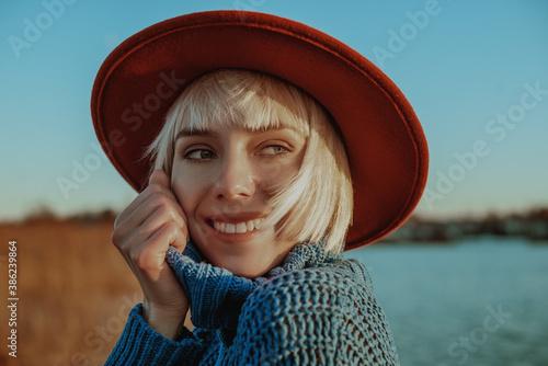 Canvas Happy smiling blonde girl wearing orange hat, blue knitted turtleneck sweater, posing outdoors