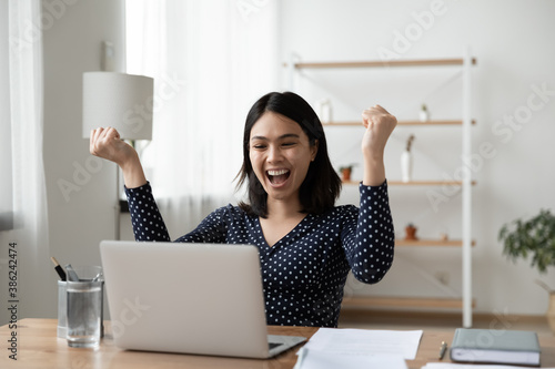 Fototapeta Excited young Vietnamese woman sit at desk at home office triumph reading good unexpected news or email on laptop. Overjoyed asian female look at computer screen feel euphoric win lottery online. obraz