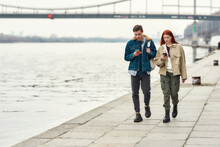 Full Length Shot Of Two Teenagers Totally Absorbed In Their Smartphones, Ignoring Each Other While Walking Along The Riverside Together