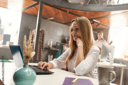 A fashionably dressed middle age blondy smiling while working with her laptop si Wallpaper Mural