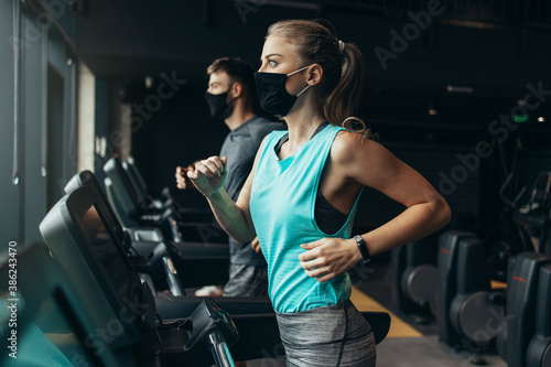 Obraz Young fit woman and man running on treadmill in modern fitness gym. They keeping distance and wearing protective face masks. Coronavirus world pandemic and sport theme. - fototapety do salonu