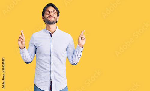 Leinwand Poster Handsome hispanic man wearing business shirt and glasses gesturing finger crossed smiling with hope and eyes closed