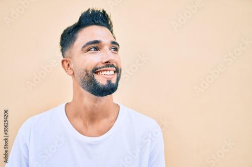 Young arab man smiling happy walking at the city. Wallpaper Mural