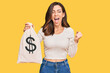 Young brunette woman holding dollars bag screaming proud, celebrating victory and success very excited with raised arms