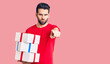 canvas print picture Young handsome man with beard holding gift pointing with finger to the camera and to you, confident gesture looking serious