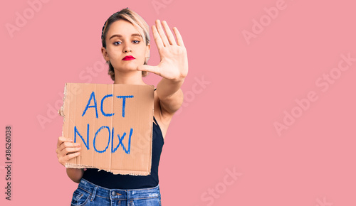 Obraz na plátne Young beautiful blonde woman holding act now banner with open hand doing stop si