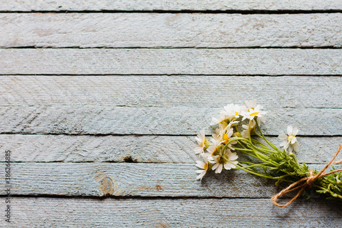 Obraz na plátně bouquet of knitted little field daisies lie on an old light blue wooden background top view, copy space