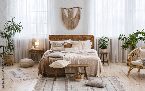 Rustic home design with ethnic boho decoration. Bed with pillows, wooden furniture - 386270425