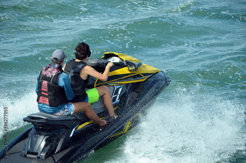 Fototapeta Two young man riding tandem on a speeding jetski