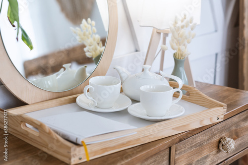 Obraz Free time at home and hot drink. Tea in kettle, cups for two on tray with notepad or book on wooden cosmetic table - fototapety do salonu