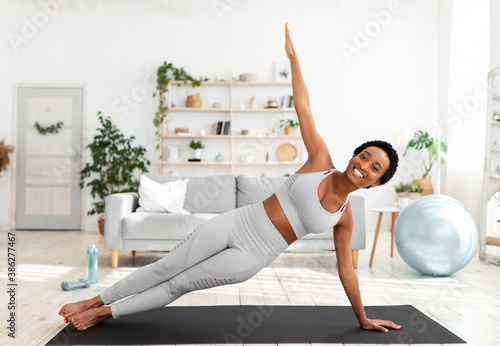 Foto Young African American woman doing strength exercises on mat in living room