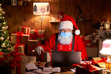 Old Bearded Santa Claus Wearing Face Mask, Holding Gift Box On Xmas Eve Sitting At Cozy Home Table Late In Night Using Laptop Computer. Merry Christmas Covid 19 Coronavirus Social Distance Concept.