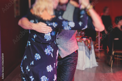 Couples dancing traditional latin argentinian dance milonga in the ballroom, tan Canvas Print