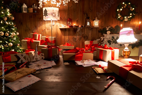 Canvas Print Santa Claus workshop home wooden decorated table with Merry Christmas tree, decor, wrapped gifts presents boxes on holiday eve in cozy home interior late in night with lamp light on xmas background