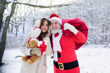 Santa Grandfather And Daughter Helper Girl Deliver Christmas Gifts In Snowy Winter Mountain. New Year And Xmas Is Coming.