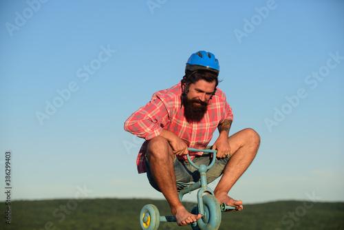 Fotografía Funny man on a childrens bike. Nerdy cyclist riding.
