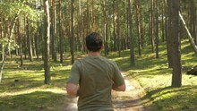 Young Man Running In The Forest Trail Under The Shades Of Tall Trees Near The Arendel Village In Zagorow, Poland. - Tracking Shot