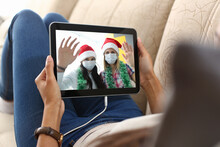 Woman Lying On Couch Communicates Through Tablet Screen With Friends In Protective Masks And Santa Hats. Celebrating New Year And Christmas During Covid-19 Pandemic.