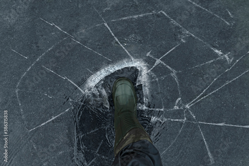Fotografie, Obraz Fisherman foot on broken cracked thin ice at lake
