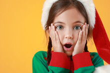 Surprised Little Girl Dressed As Elf On Color Background