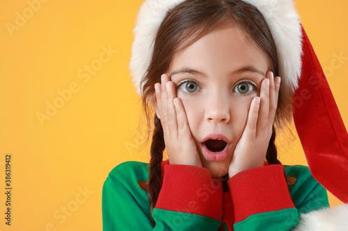 Fotografija Surprised little girl dressed as elf on color background