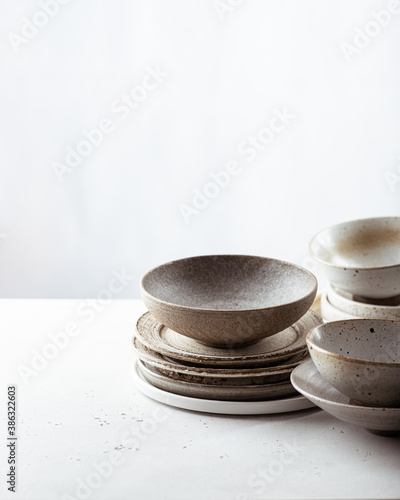 Leinwand Poster handicraft ceramics, empty craft ceramic bowl and plates on light background