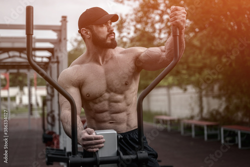 handsome strong young athlete bearded man in cap standing on fitness exercise street sport equipment