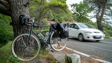 Touring Bicycle Standing Near The Road With Back Panniers