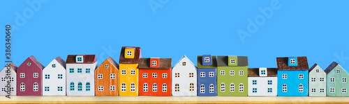 Valokuva Row of wooden miniature colorful retro houses on blue solid background