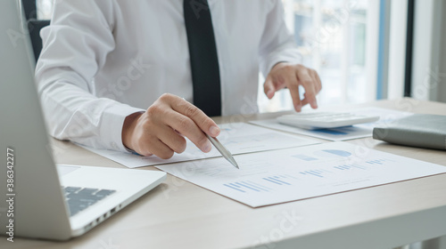 Fototapety, obrazy: The businessman hand sits at their desks and calculates financial graphs showing the results of their investments planning the process of successful business growth