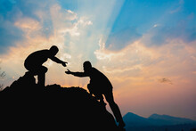 Teamwork Success Concept. Hiker Help Each Other Silhouette In Mountains With Sunlight.